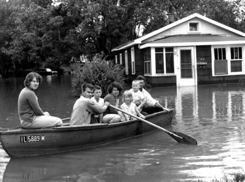 Sept. 15, 1961: The Smith family rows down Burlington Avenue with their flooded home in the background.