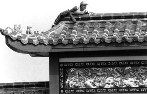 Sept. 20, 1990: Worker Jose Suaso Mermudes crouches on the pagoda-like roof of a Chinese restaurant in Lisle while wiping off excess grout after a new tile roof was installed.