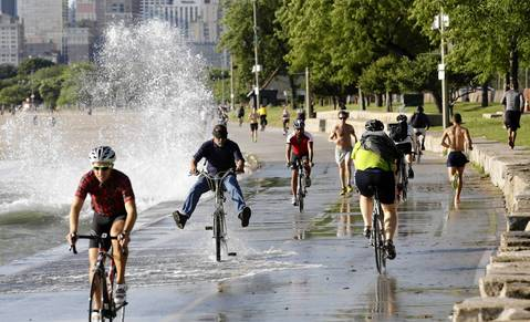 A cyclist raises his feet to avoid water as high waves on Lake Michigan crash onto the Lakefront Trail near Fullerton Avenue.