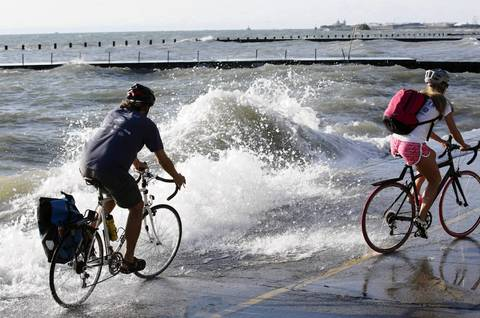 A bicyclist rides close to the edge and crashing waves of the Lakefront Trail near Fullerton Avenue.