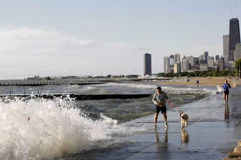 A wave crashes near a man and his dog on the Lakefront Trail near Fullerton Avenue.