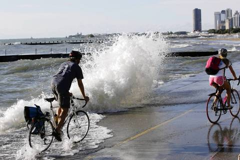 A waves crashes in front of a bicyclist on the Lakefront Trail near Fullerton Avenue.