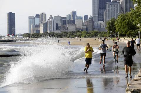A runner dodges a wave on the Lakefront Trail at Fullerton Avenue.