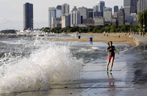 A runner goes around a wave hitting the Lakefront Trail between Fullerton Avenue and North Avenue beach.