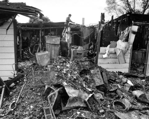 May 21, 1984: Investigators search the debris of a Hoffman Estates house Sunday after a fire that killed Edward Lewis and his wife, Amelia. A portion of the roof over the living room and kitchen collapsed as firemen arrived.
