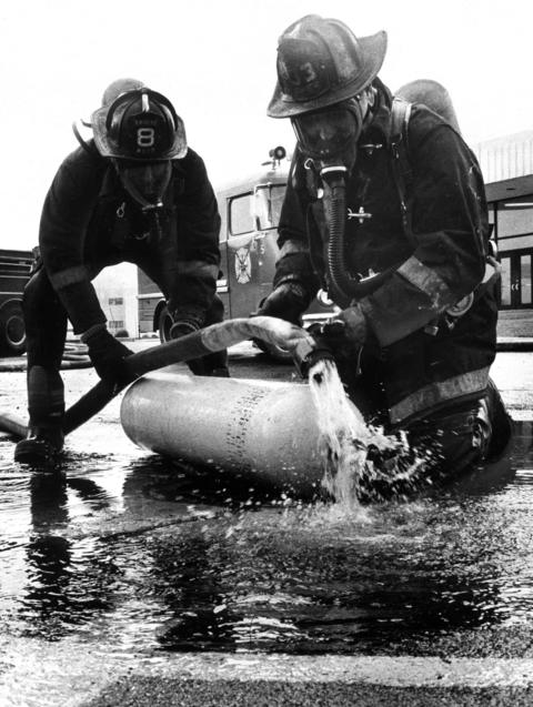 Jan. 22, 1980: After breaking off the valve to release the tank's contents, masked firefighters dilute liquid chlorine steaming into a sewer in Hoffman Estates. Fumes from a leak in the tank sent 53 people at Hoffman Estates High School to hospitals.