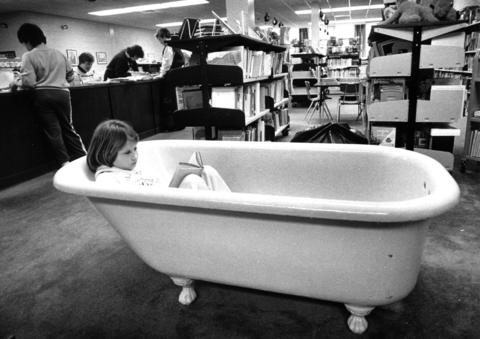 Feb. 8, 1988: Karen Tournier, 9, of Hoffman Estates, cuddles up to read in a bathtub inside the Learning Resource Center at Thomas Jefferson School. The tub is used to encourage students to read.