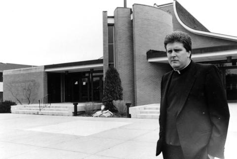 March 26, 1987: Father Jack Clair, of St. Hubert Church, stands in front of his parish church. In the church's area the population grew so large that four more churches were built.