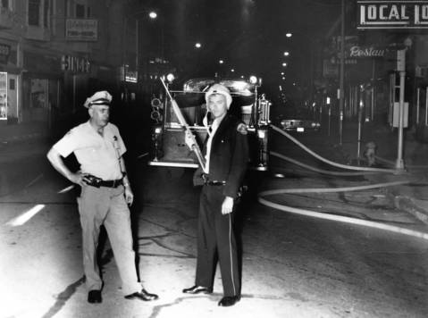 "Aug. 4, 1967: Police guard Elgin streets during an ""outbreak of riots and firebombing."" The caption does not provide details about the cause of the riots."