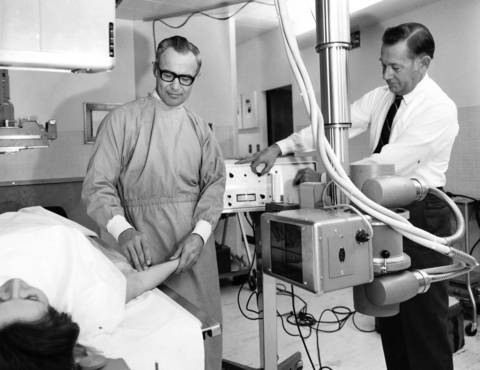 Feb. 17, 1970: Dr. Thomas A. Heenahan, chief radiologist at Sherman Hospital in Elgin, adjusts an electronic dye injector, while Dr. Myron E. Elliott, the attending physician, prepares the injection site.