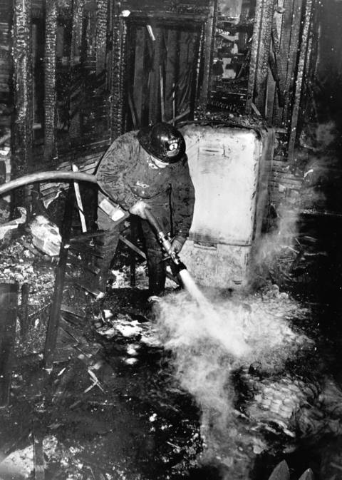 Feb. 28, 1970: An Elgin firefighter continues to pump water into the remains of a three-story apartment building. Three people died in the fire.
