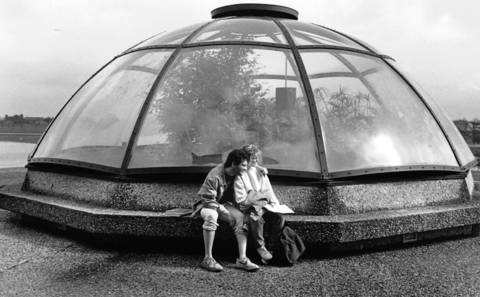 March 23, 1990: Harry Hoffman and Katrina Pederson relax near a greenhouse on the Elgin Community College campus.