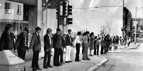 "Oct. 29, 1975: Elgin residents participate in an event resembling the yet-to-occur ""Hands Across America."" The original caption says the Elgin event, which took place along Chicago Street, was to mark the 89th birthday of the Statue of Liberty."