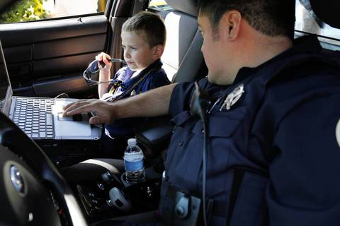 """Adam Brodersen, 7, (left) gets his chance to sit in a police squad car at Buffalo Grove Police Department. He had just been """"sworn in"""" by the department, and was about to ride with police officer Mike Martin (right). Adam suffers from a heart ailment and dreams of becoming a cop."""