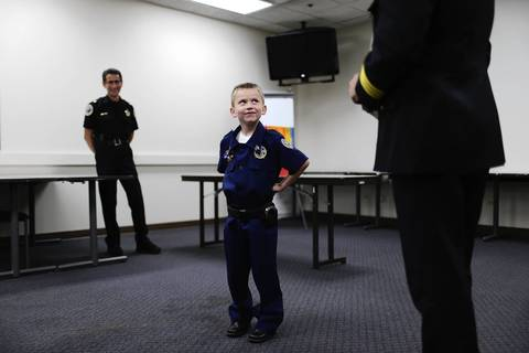 """Adam Brodersen, 7, (center) is introduced to a gathering of people before being """"sworn in"""" as a sergeant in the Buffalo Grove Police Department by Police Chief Steven Casstevens (right). At left is Commander Jim Newton. Adam suffers from a heart ailment and dreams of becoming a cop."""