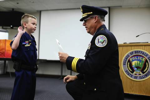 """Adam Brodersen, 7, (left) is """"sworn in"""" as a sergeant in the Buffalo Grove Police Department by Police Chief Steven Casstevens. Adam suffers from a heart ailment and dreams of becoming a cop."""
