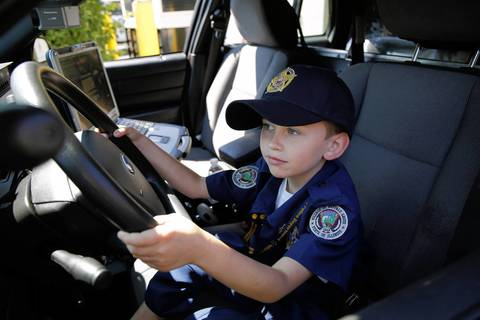"""Adam Brodersen, 7, gets his chance to sit in the driver's seat of a police squad car at the Buffalo Grove Police Department. He had just been """"sworn in"""" by the department and was about to ride with an officer. Adam suffers from a heart ailment and dreams of becoming a cop."""