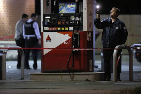 Police investigators work the scene of a fatal shooting at a gas station at 116th Street and Michigan Avenue.