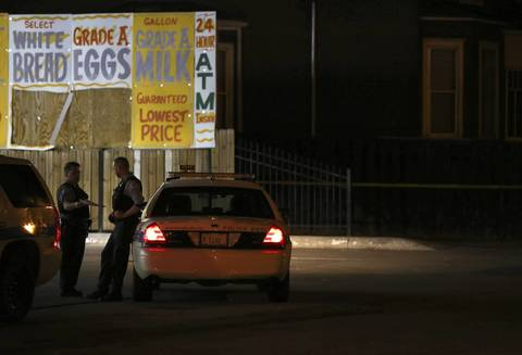 Police officers talk at the scene of a fatal shooting at a gas station at 116th Street and Michigan Avenue.