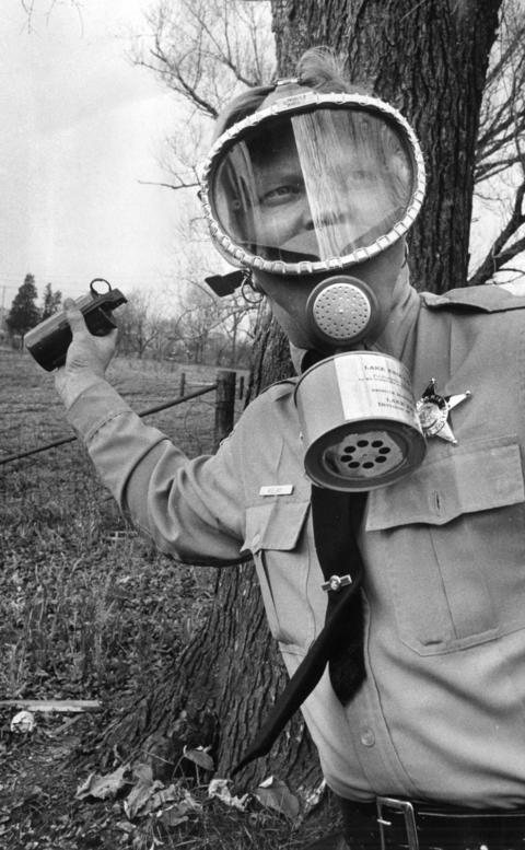 Jan. 7, 1971: Patrolman Royce E. Lacy cocks his arm, ready to lob a teargas grenade at a target during a training session staged by the Deerfield Police Department. The 2-hour sessions were held on a farm, located on the 400 block of Sanders Road.