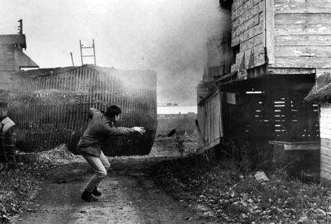 "Nov. 17, 1970: A Deerfield police officer watches smoke gush from an abandoned farmhouse after lobbing a teargas canister inside. The building, hiding a ""dummy"" fugitive, was used during a Deerfield Police Department training session."