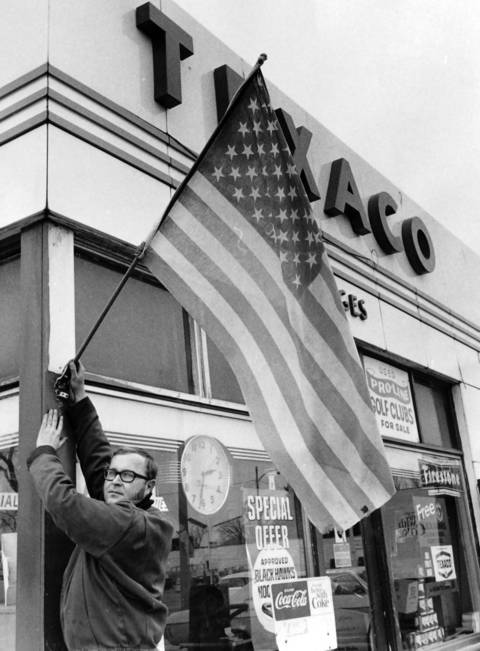 Jan. 3, 1972: Thomas Koppelman, manager at Midges Texaco Gas Station in Deerfield, raises Old Glory.