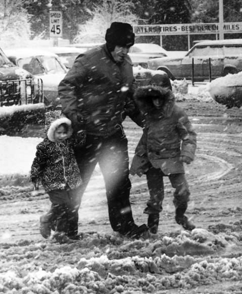 Dec. 14, 1973: A man helps his children across the street near Waukegan and Lake Cook Roads. School was canceled due to the weather.