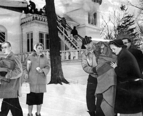 Jan. 30, 1959: The scene of a fire at the Glen Ellyn Acres Nursing Home. One of the victims, Anna O'Malley, is escorted to an ambulance as fireman battle the blaze in the background.