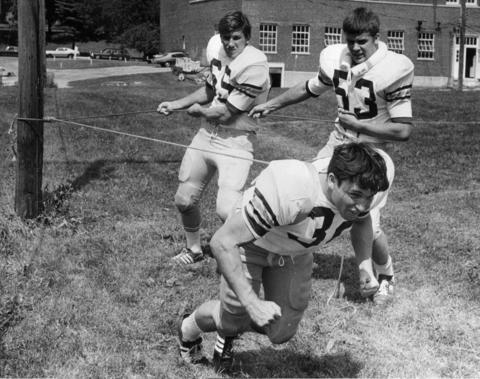 Aug. 31, 1970: John Pullen of the College of DuPage pulls teammates Tom Daman and Joe Nelson with a device that builds muscles in the legs and back.