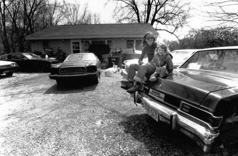 April 26, 1989: Martha Douglas and her granddaughter, Yvonne, sit on one of the eight cars parked in the front lawn of her Highland Park home on April 26, 1989.
