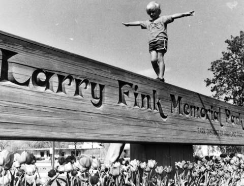May 17, 1984: A child balances on the sign at Larry Fink Memorial Park on May 17, 1984. The park is named after a man who died in a 1979 plane crash.