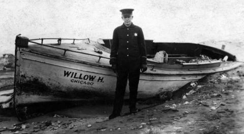 "A Chicago police officer poses by a ""rum runner,"" a boat confiscated with beer on board in February of 1920."