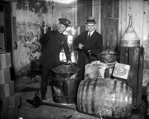 Officer William Murphy, left, and Capt. James E. McCann perform a booze raid at 639 Roosevelt Rd. in this undated photo.
