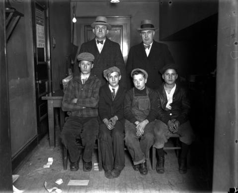 Boy bootleggers Adolph Heise, 16, from left, Nick Pappas, 13, Lawrence Farley, 14, and Harry Hammond, 16, sit in front of officers August Ptack and William Higgins at the Federal Building on Nov. 30, 1928. The boys were caught pulling a wagon containing 24 bottles of beer they were delivering to Hammond's mother, who also had 21 cases of beer, 50 gallons of wine, and two quarts of gin in her possession.