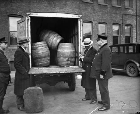 Officer Albert Majeske, from left, John Seevy, John Boland and Captain Willard L. Malone, uncover a truck filled with barrels of alcohol in May of 1929.