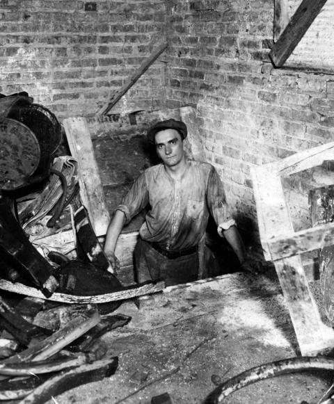 "George Groth, a Prohibition department ""break-up"" man, is shown standing in a trap door leading into a tunnel where liquor was transported in September of 1930."