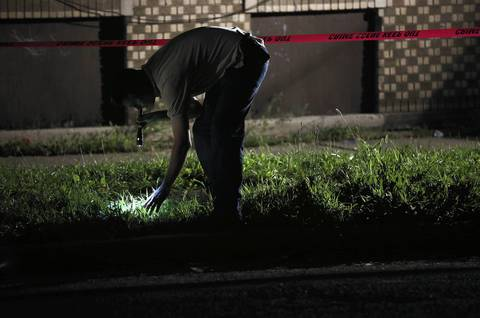 A police investigator searches the grass outside the apartment where a 16-year-old boy was shot and killed through an open window at 68th Street and Artesian Avenue.