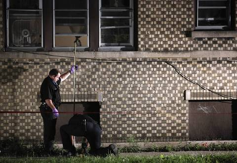 Police investigate the scene where a 16-year-old boy was shot and killed through an open window inside a first-floor apartment at 68th Street and Artesian Avenue in the Marquette Park neighborhood.