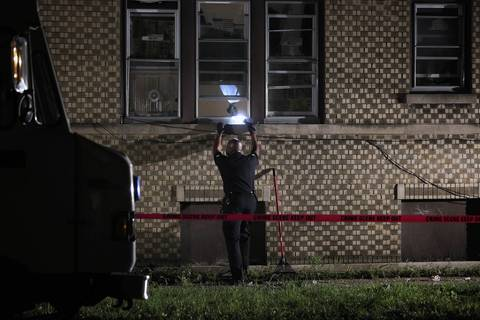 Police investigate the scene where a 16-year-old boy was shot and killed through an open window inside a first-floor apartment at 68th Street and Artesian Avenue.
