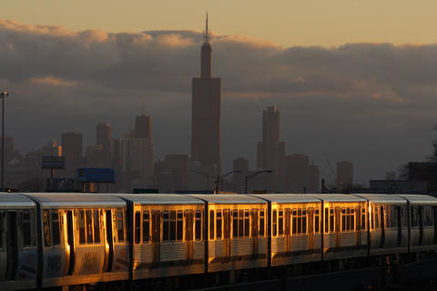A bank of clouds holds steady over the city as the sunset hits the CTA train.
