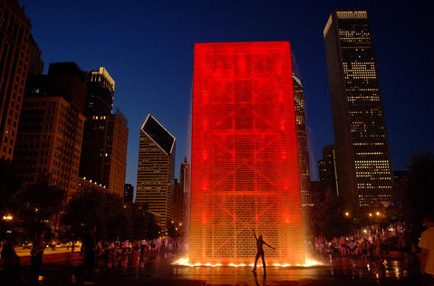 A girl poses in front of Crown Fountain in Millennium Park.
