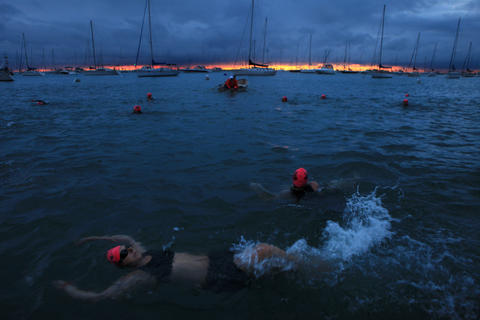 As the sun comes up over Lake Michigan, triathletes begin the swim portion of the 27th Chicago Triathlon.