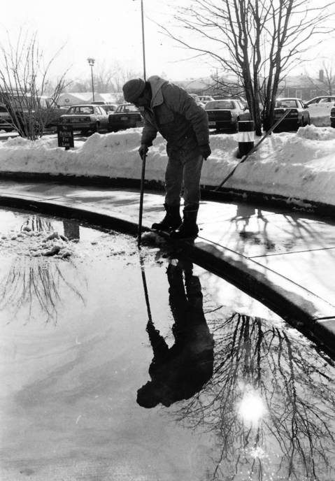 Jan. 14, 1991: Jesse Vela catches a reflection of himself while clearing snow and ice from a sewer drain in Hinsdale on Jan. 14, 1991.