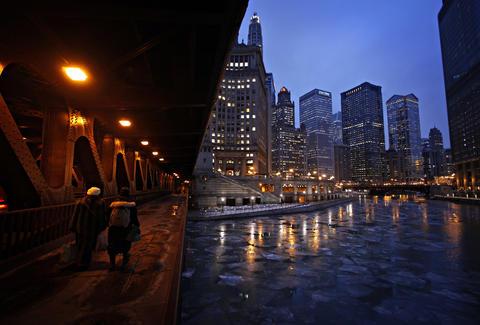 Pedestrians walk under the Michigan Avenue bridge over a frozen Chicago River.