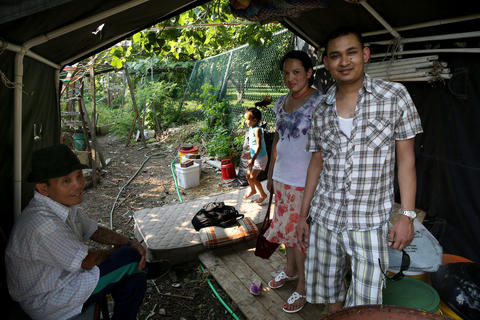 From left, Ngui Thay from Burma; and the Darnal family from Bhutan, Diya, 3 and her mother Sha and father Deoki, take to the shade under a small shelter built in the garden by one of the refugees.
