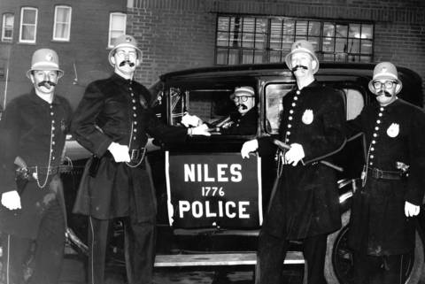 June 27, 1962: Niles police officers, dressed as the Keystone Cops, pose for a photo by an antique patrol car.