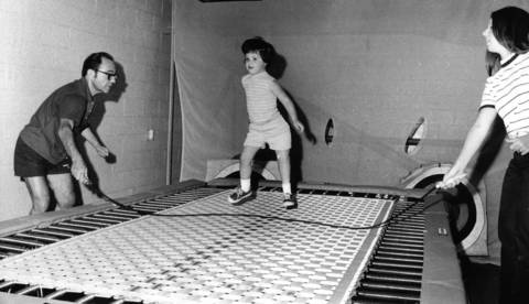 Aug. 5, 1971: Marla Bramble, who has a prosthetic left leg, uses the trampoline under the watch of instructor Ray Newman, left, at the Niles YMCA.
