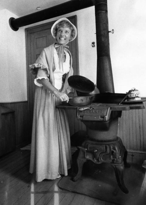 June 24, 1976: Shirley Pace displays an old wood-burning stove at Naper Settlement.