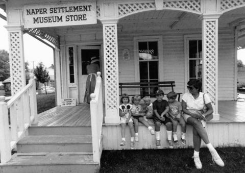 Aug. 23, 1989: Visitors sit on the front porch of the museum store at Naper Settlement.