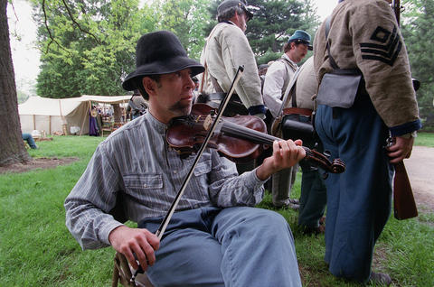 May 15, 1999: Randy Smith of Macomb plays a fiddle against a backdrop of Confederate soldiers preparing for battle at Naper Settlement's Civil War Days.